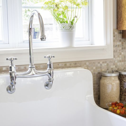 Rustic white porcelain kitchen sink with curved faucet and tile backsplash under large window